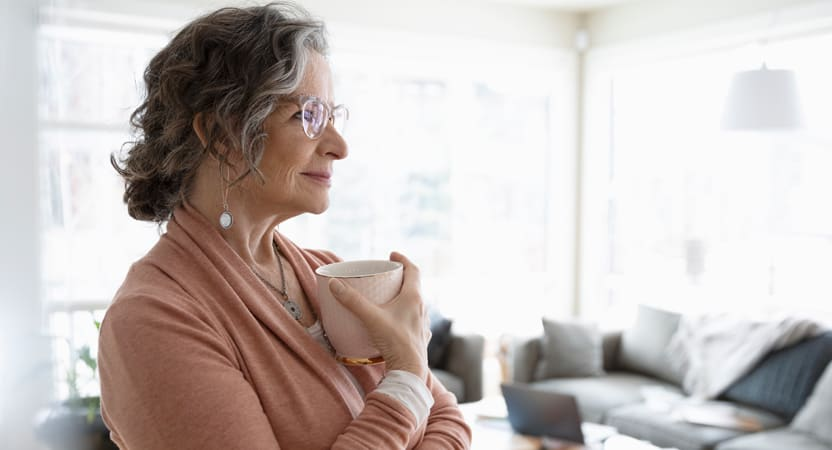 Caucasian middle aged female with glasses holding a cup